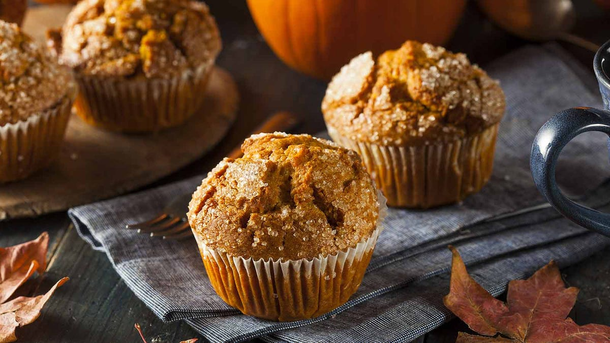 delicious pumpkin muffins sitting on a wood table surrounded by leaves, muffins, and pumpkins