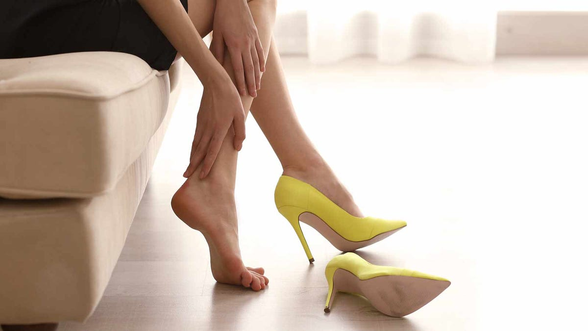woman rubbing her feet after wearing high heels all day