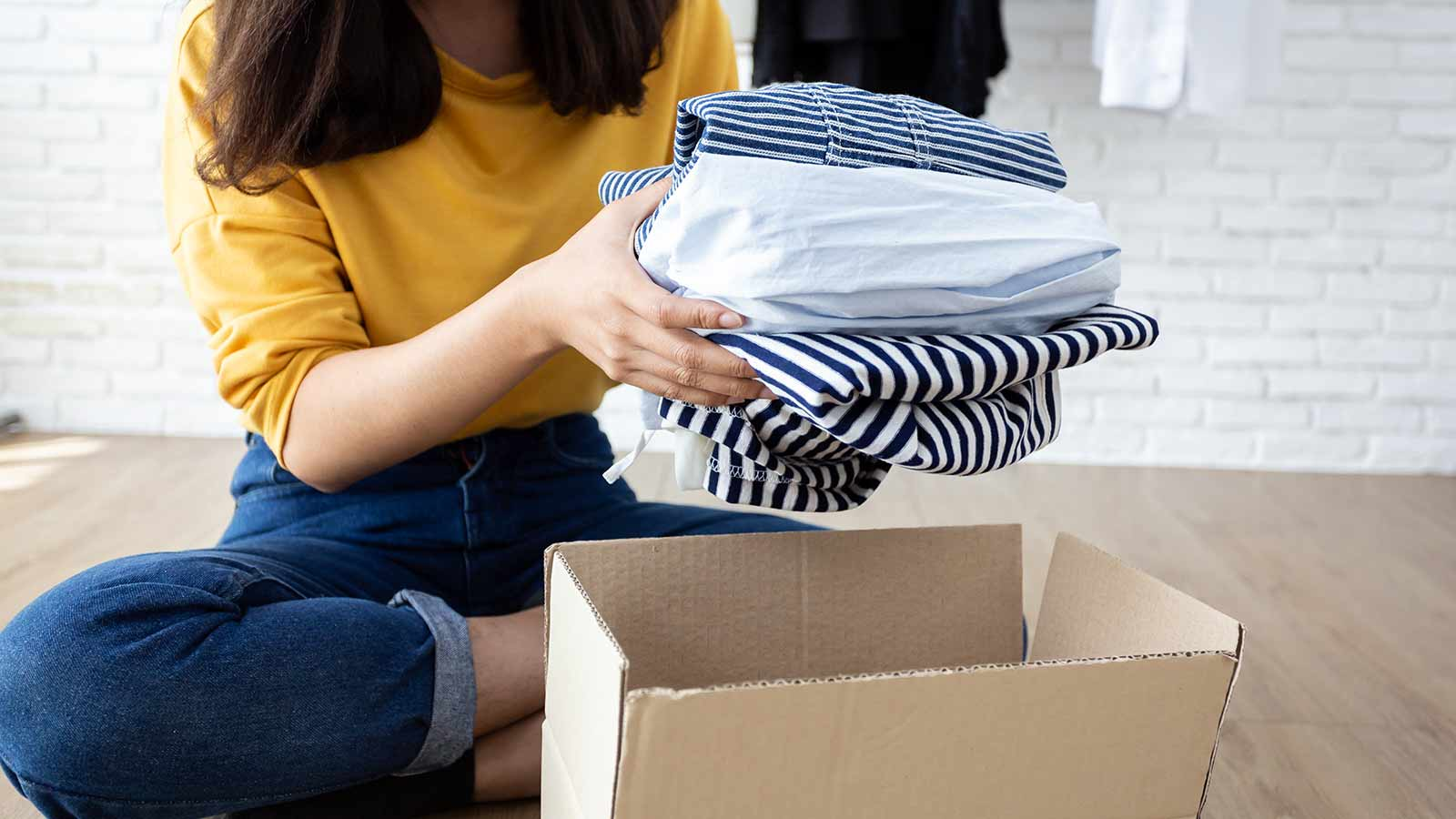 A woman sitting on the floor, putting a stack of clothes in a cardboard box.