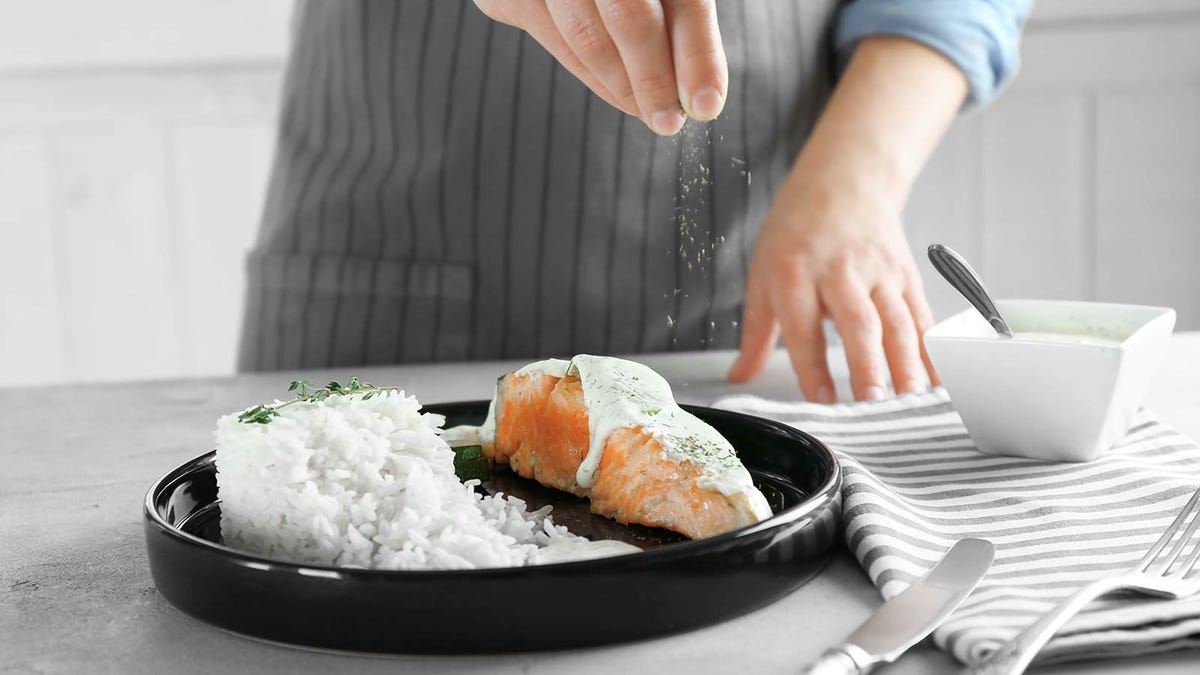 A hand sprinkling seasoning over a plate of salmon and rice.