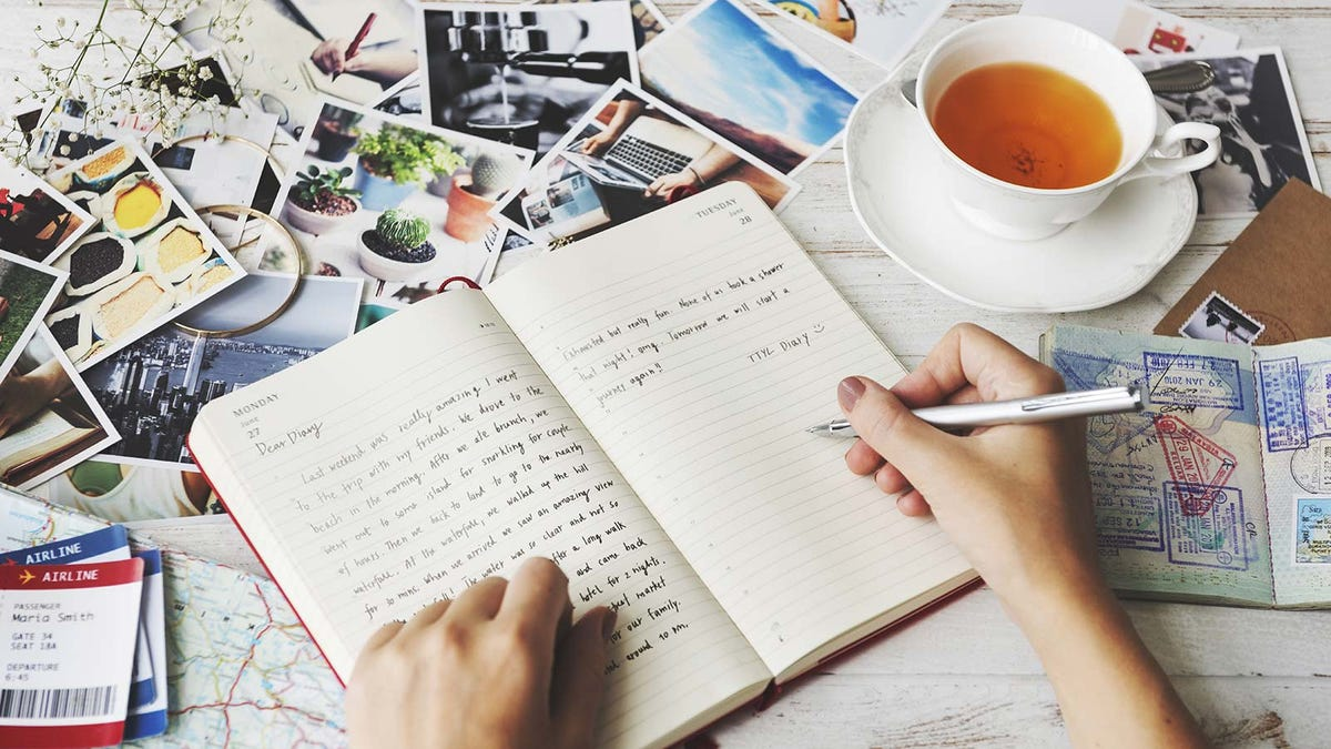 Woman writing in a travel journal on a table covered in photos and travel documents.