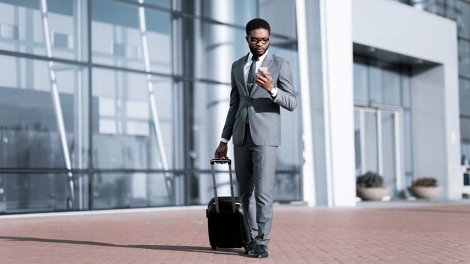Business man walking in front of an airport while checking his phone