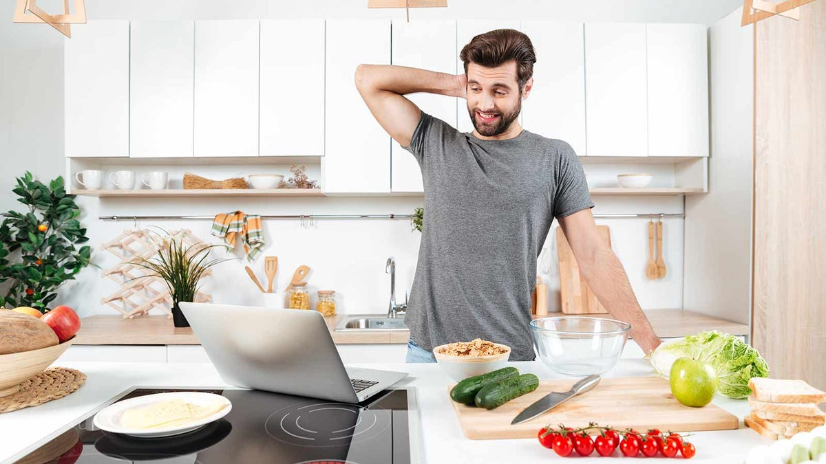 man working on a recipe in the kitchen, but frustrated because he doesn't have a Dutch oven