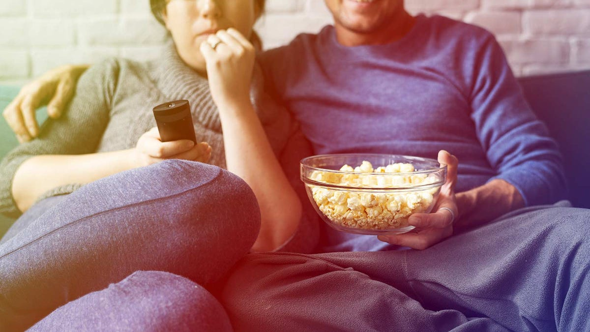 A man sitting on a couch holding a bowl of popcorn next to a woman holding a remote control.