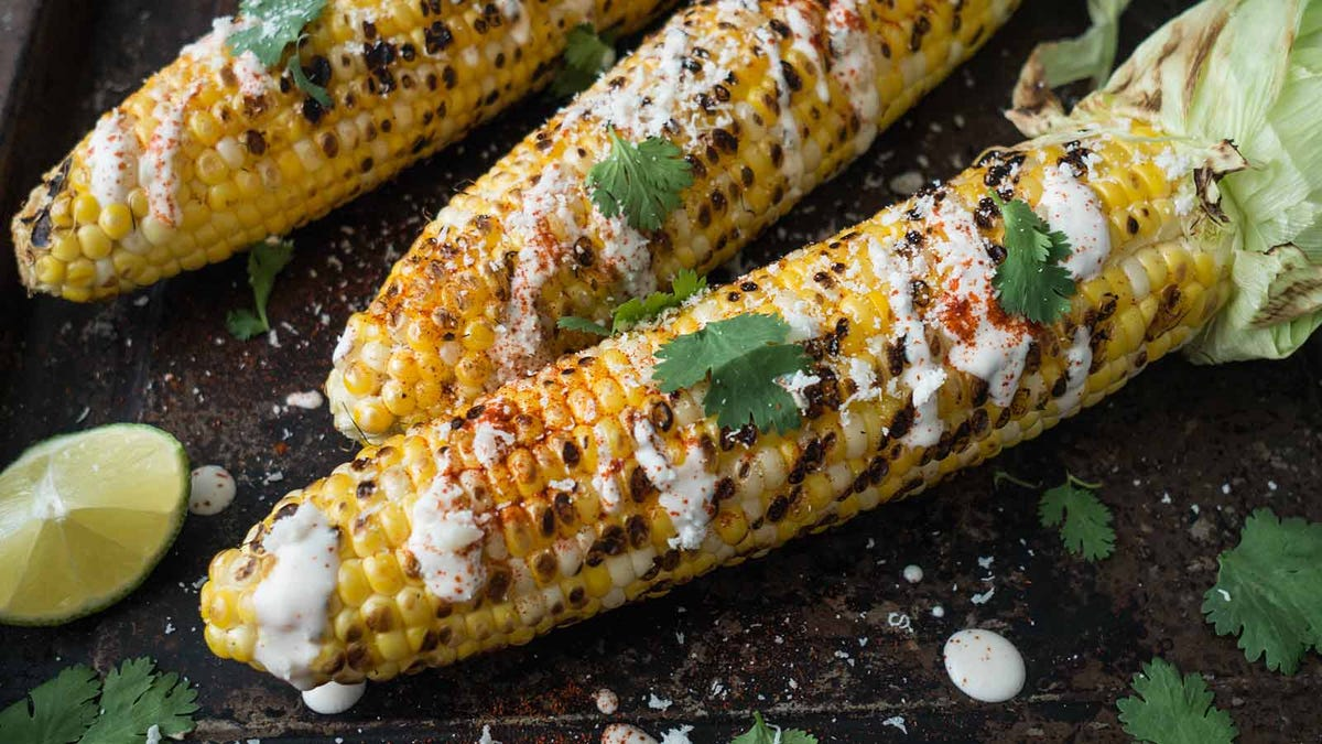 Grilled corn cobs with sauce, coriander, lime, paprika and cheese.