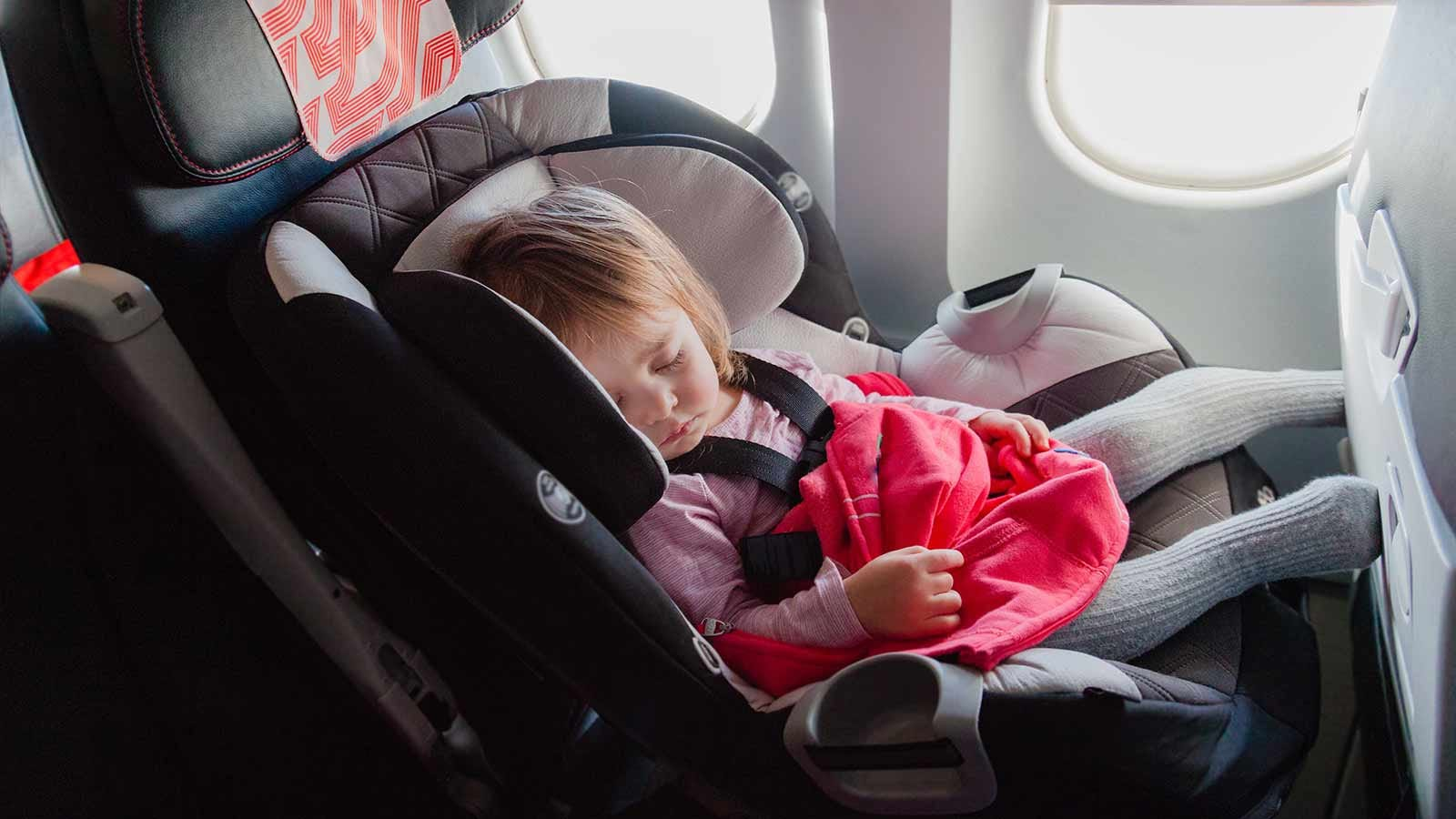A toddler sleeping in a forward-facing car seat in a window seat on a plane.
