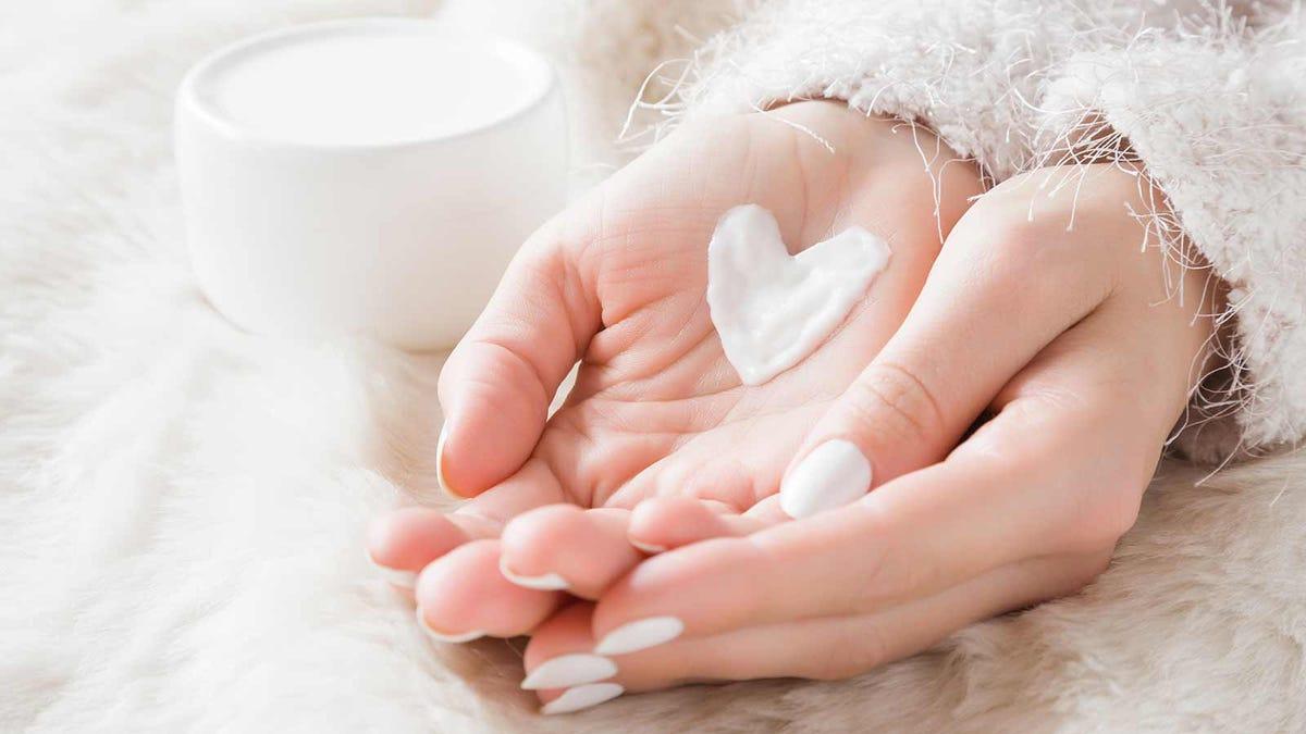 woman rubbing moisturizer onto her dry hands, the moisturizer is shaped like a heart