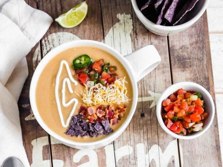 A bowl of southwestern bisque topped with jalapeno, cheese, pico de gallo, and a sour cream drizzle.