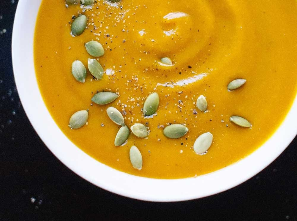 A bowl of roasted pumpkin soup with pumpkin seeds on top