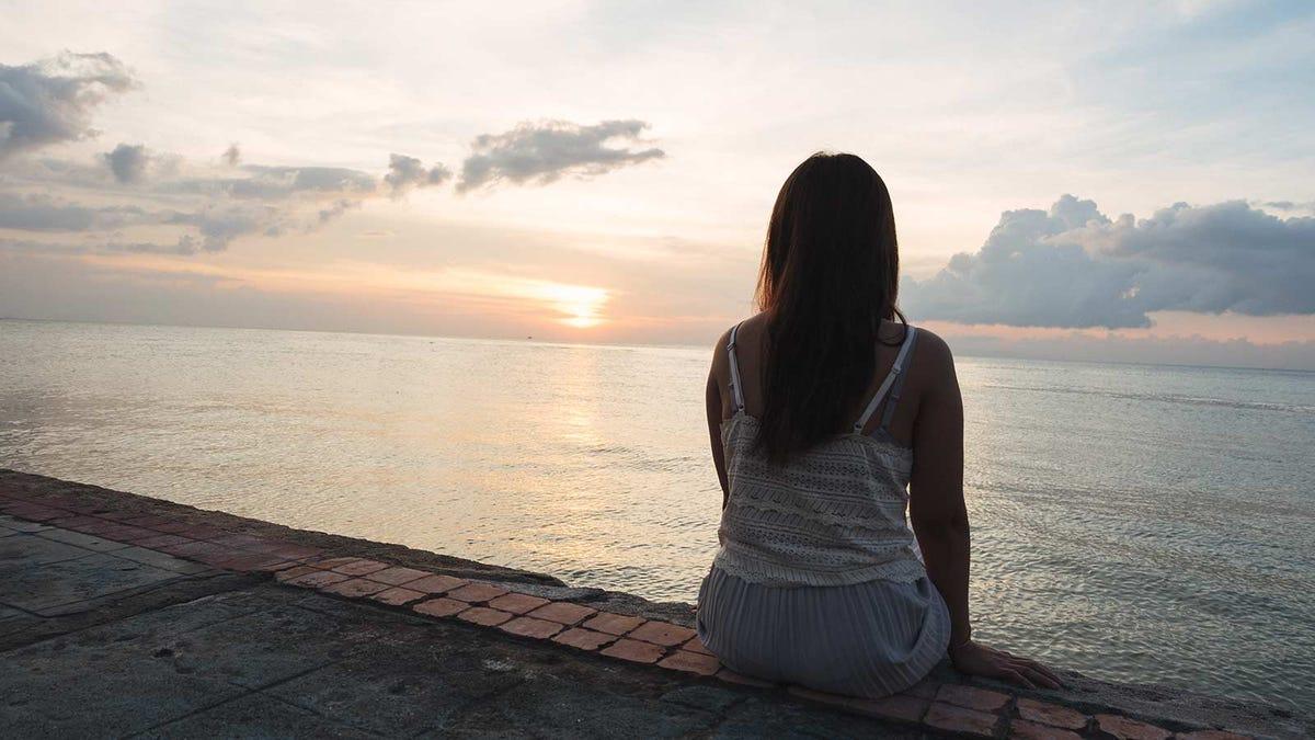 woman sitting alone on a brick wall watching the sun set
