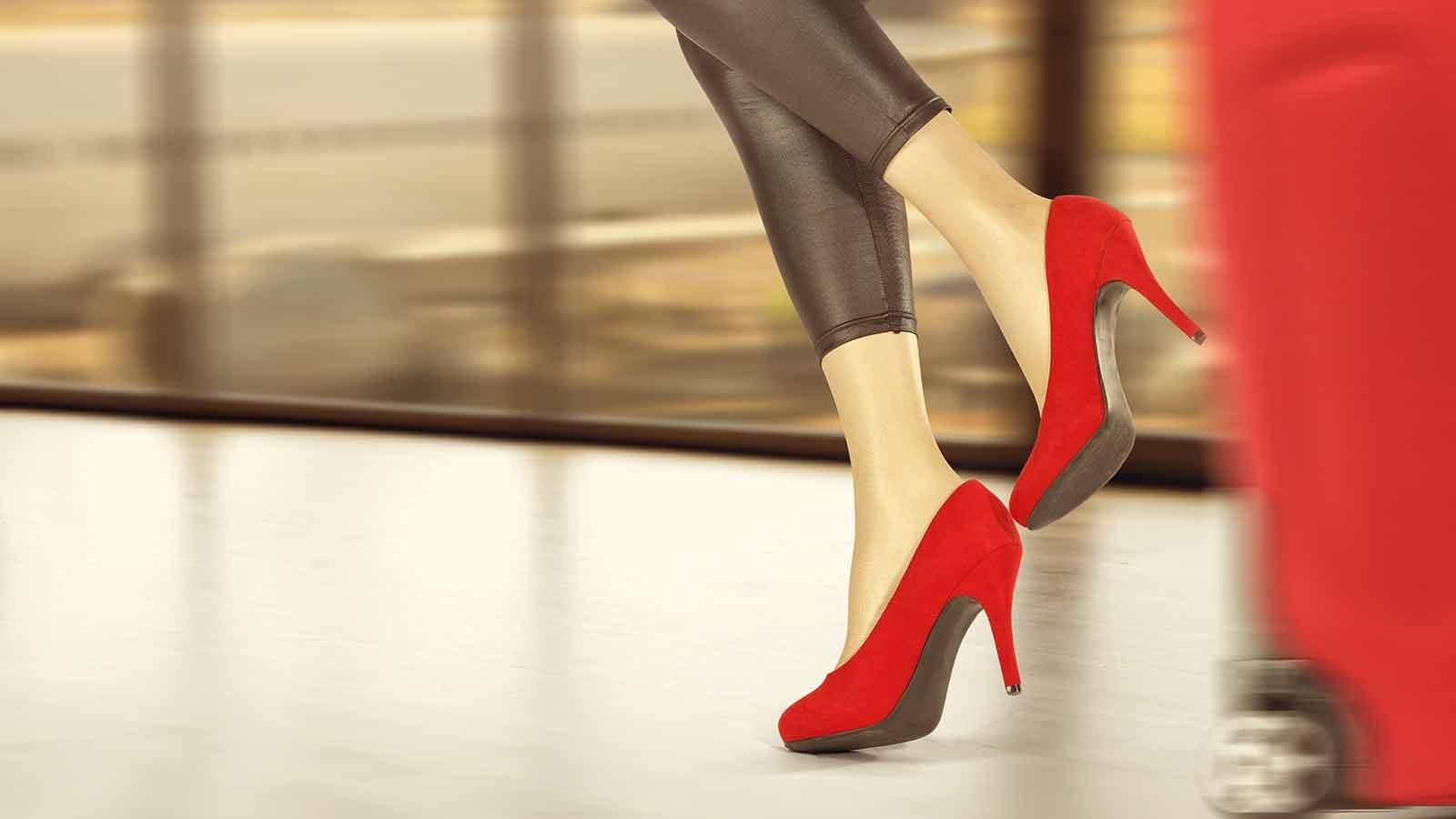 woman running down an airport walkway in heels