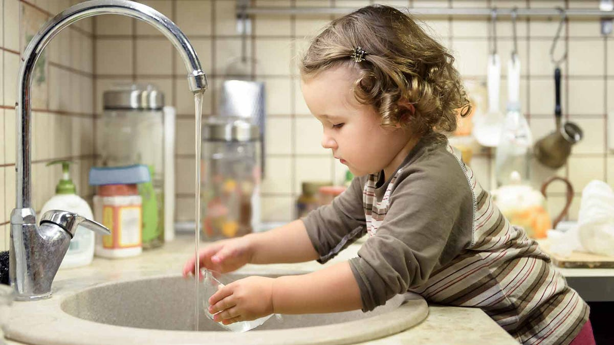 A toddler washing a dish in the kitchen sink.