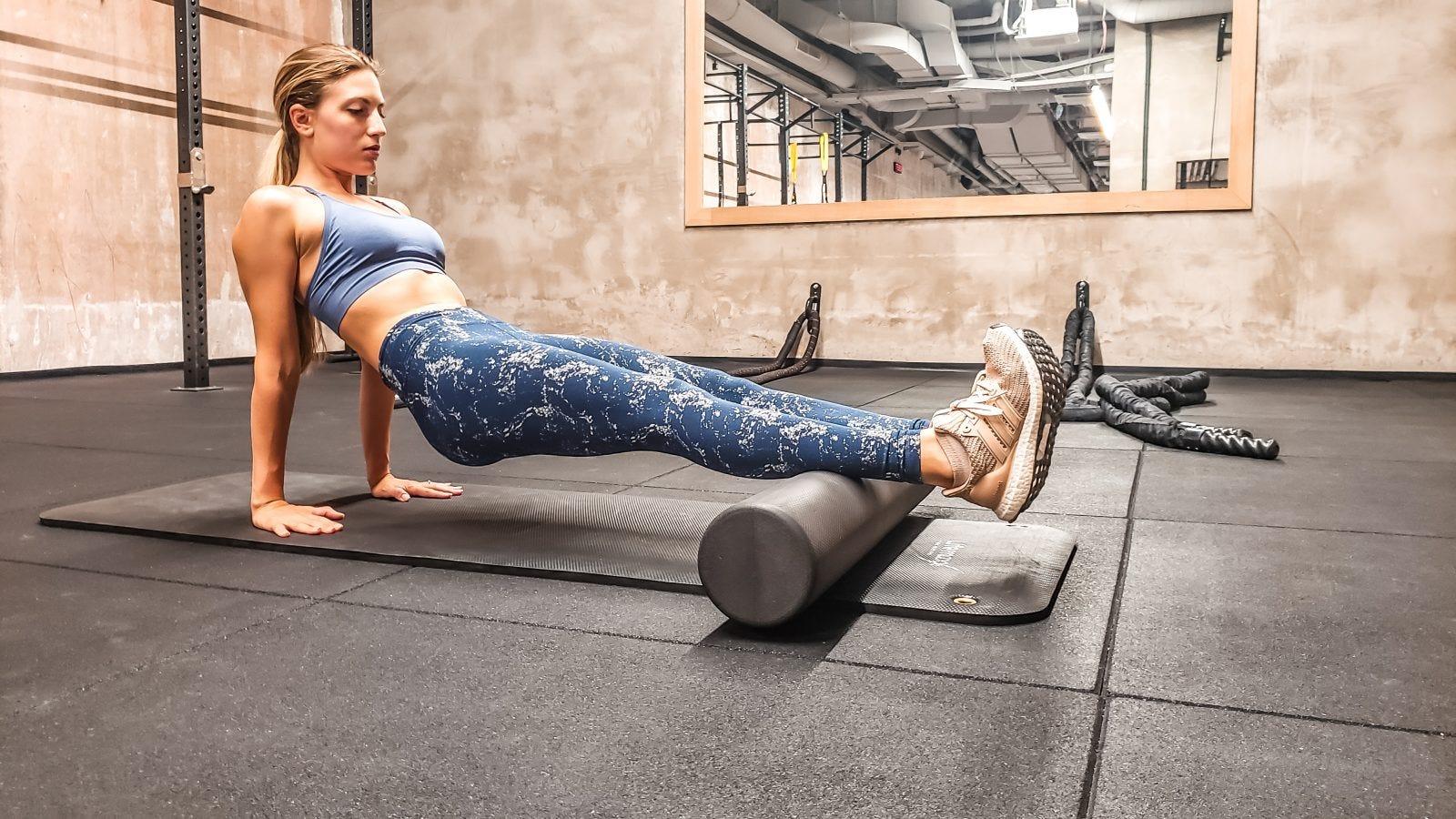 A woman in a gym foam rolling her calves.