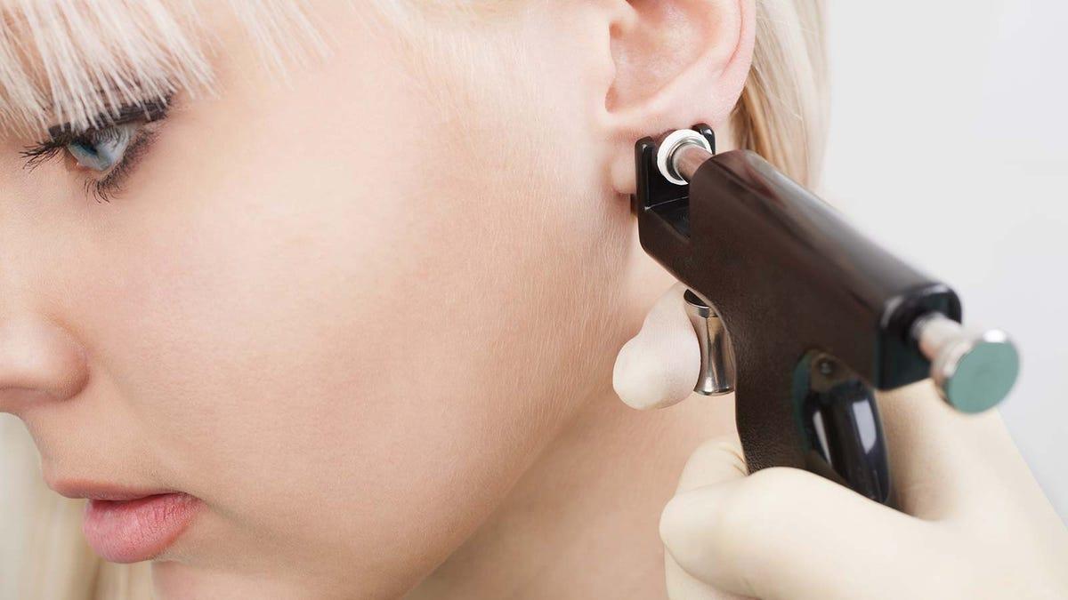 Woman getting her ears pierced by someone using a piercing gun.