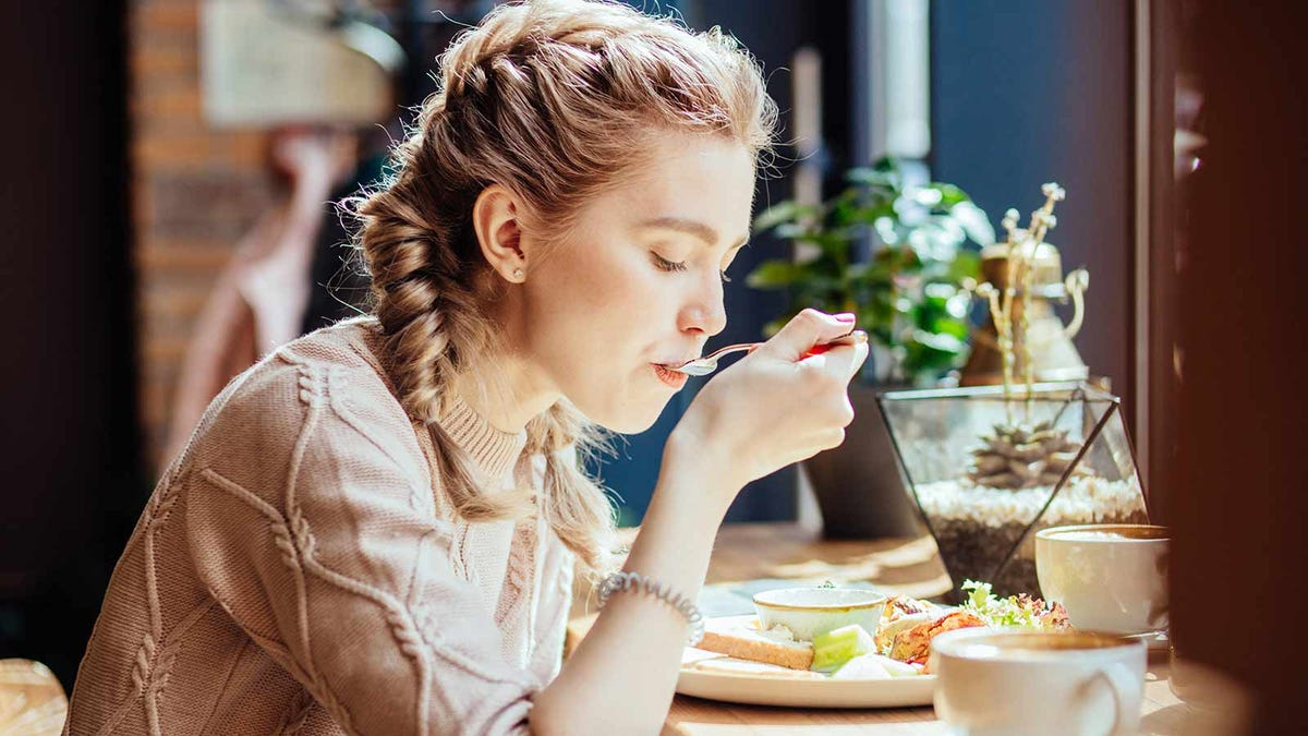 woman eating a delicious meal, focused on the flavors and presentation of the food