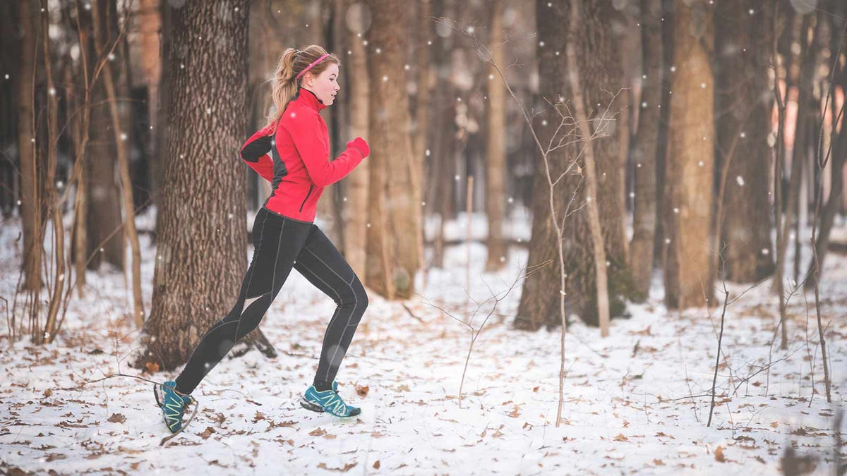 woman doing some trail running through a snowy forest