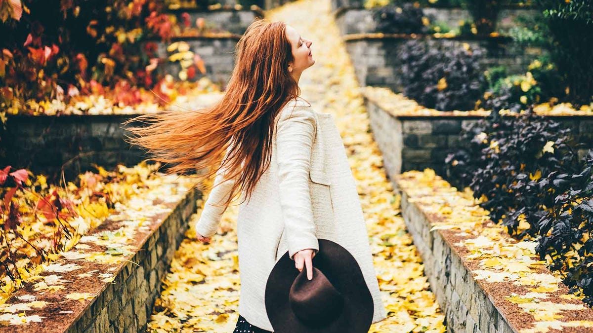Woman walking down a leaf-covered path, holding a hat.