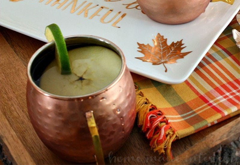 A copper mug with a mule drink and an apple and lime garnish