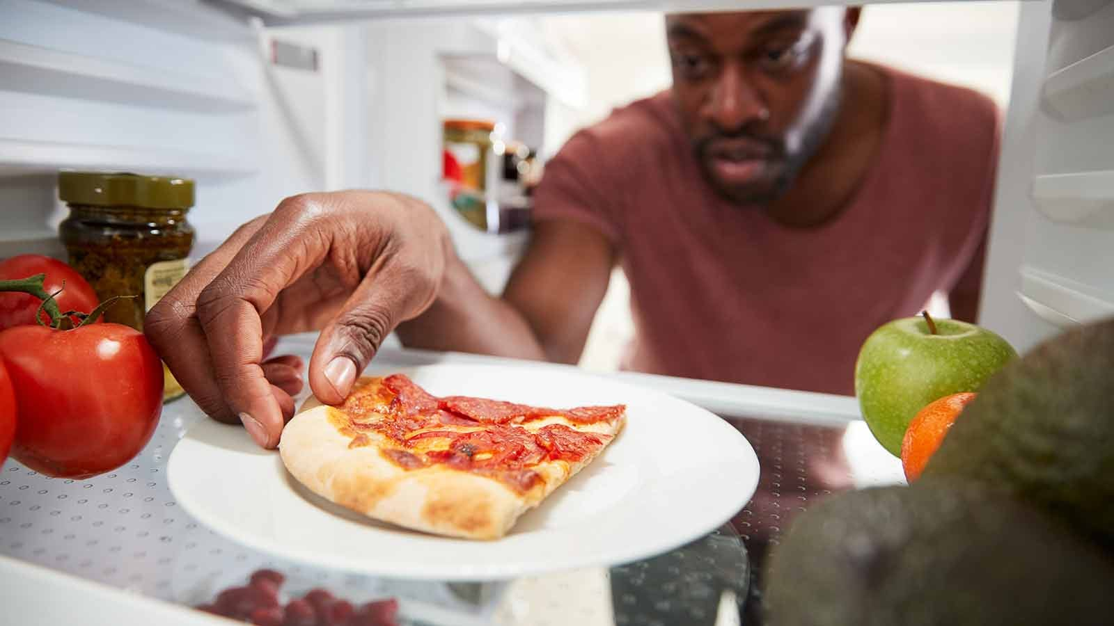 man pulling a piece of left over pizza out of the fridge