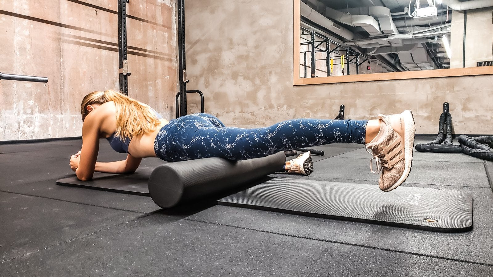A woman in a gym doing a quad roll with her left leg on a foam roller.