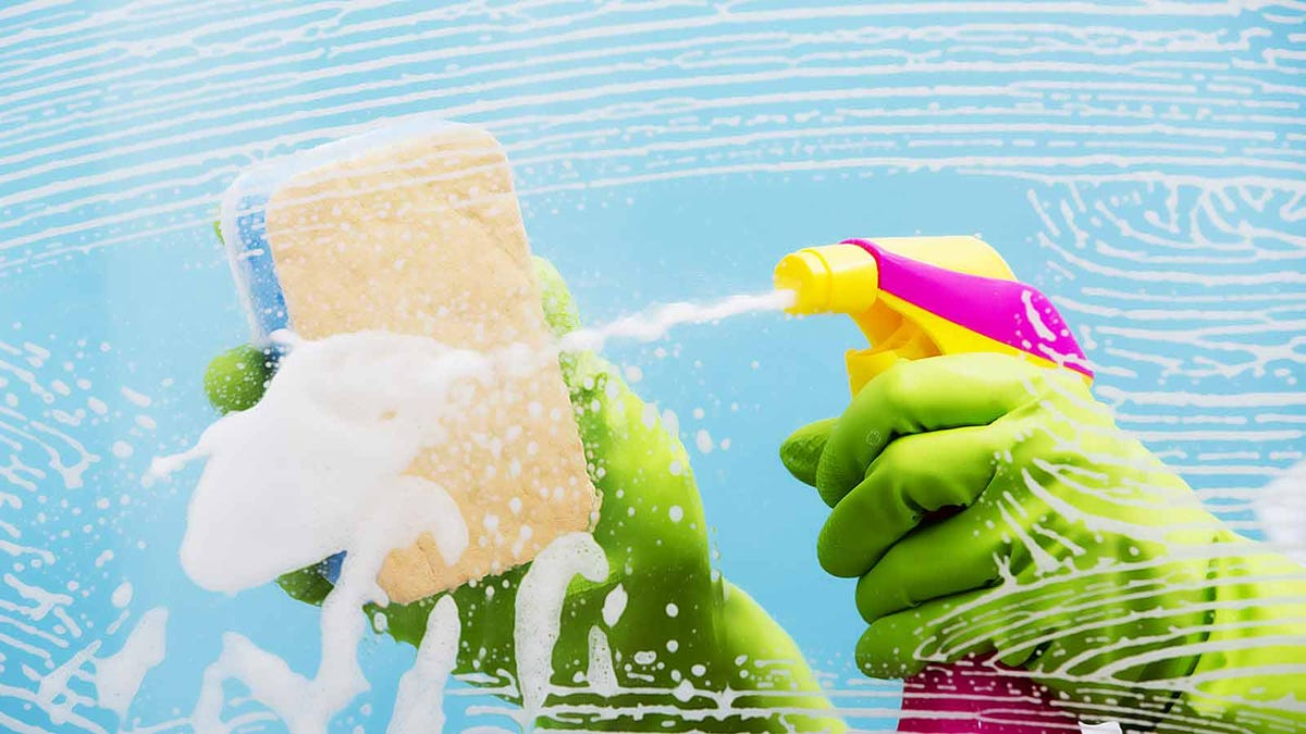 someone wearing green rubber gloves spraying cleaner on a surface and scrubbing it with a sponge