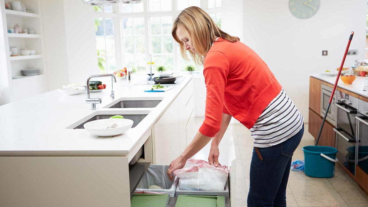 woman emptying trashcans to prepare them for cleaning