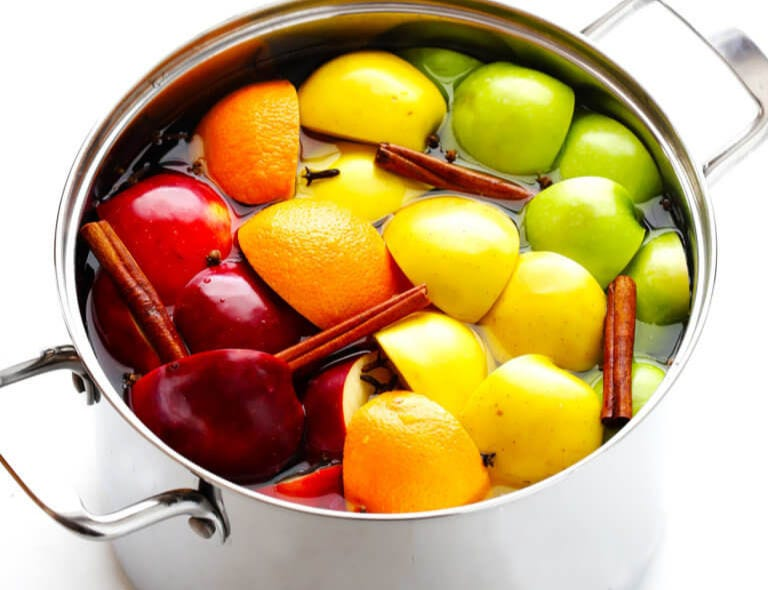 A stockpot filled with apples, oranges, cinnamon sticks and water.