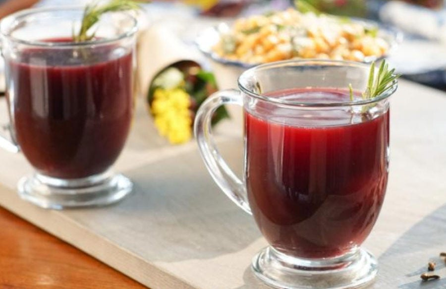 two glass mugs filled with red mulled wine and garnished with rosemary.