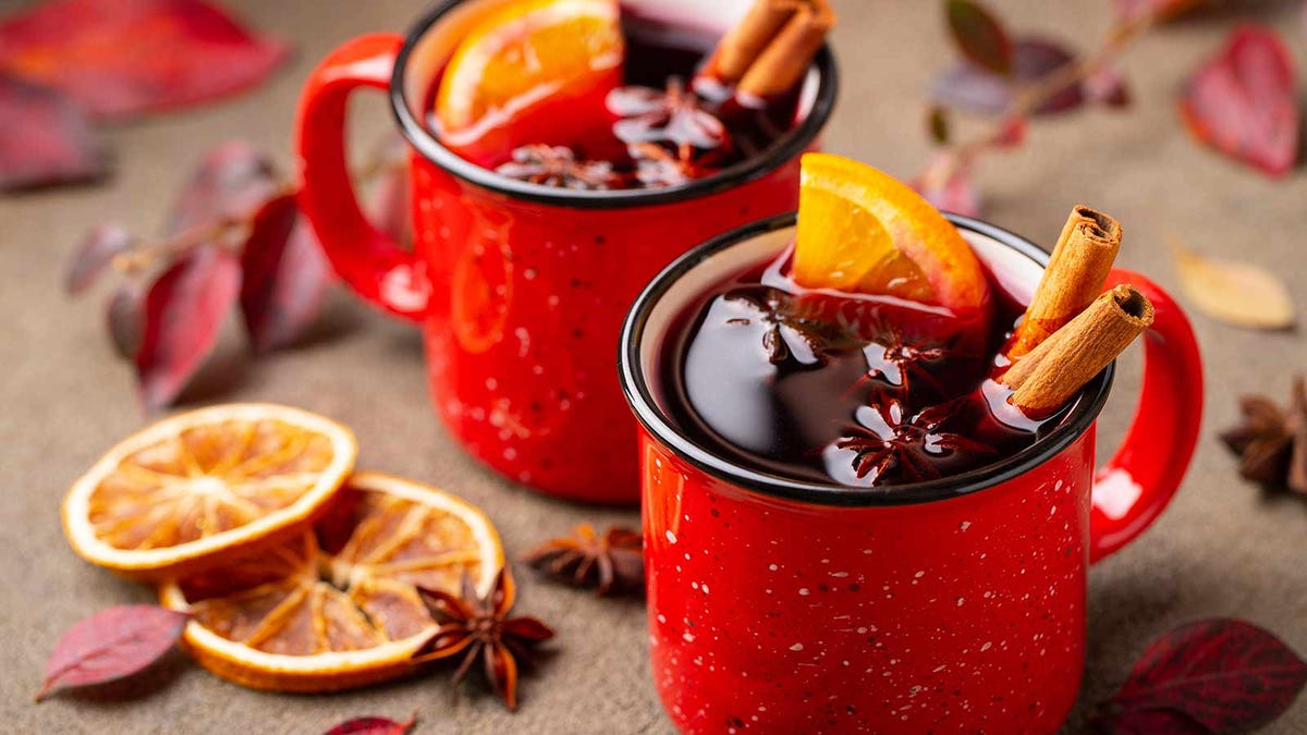 two mugs of mulled wine with orange slices and spices