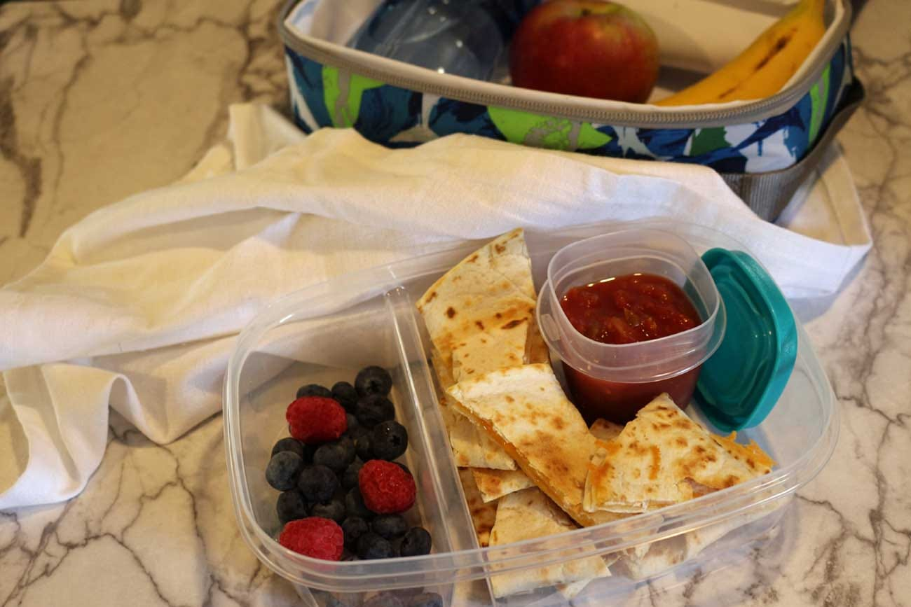 Packed lunch with cheese quesadilla, mixed berries, an apple and a banana