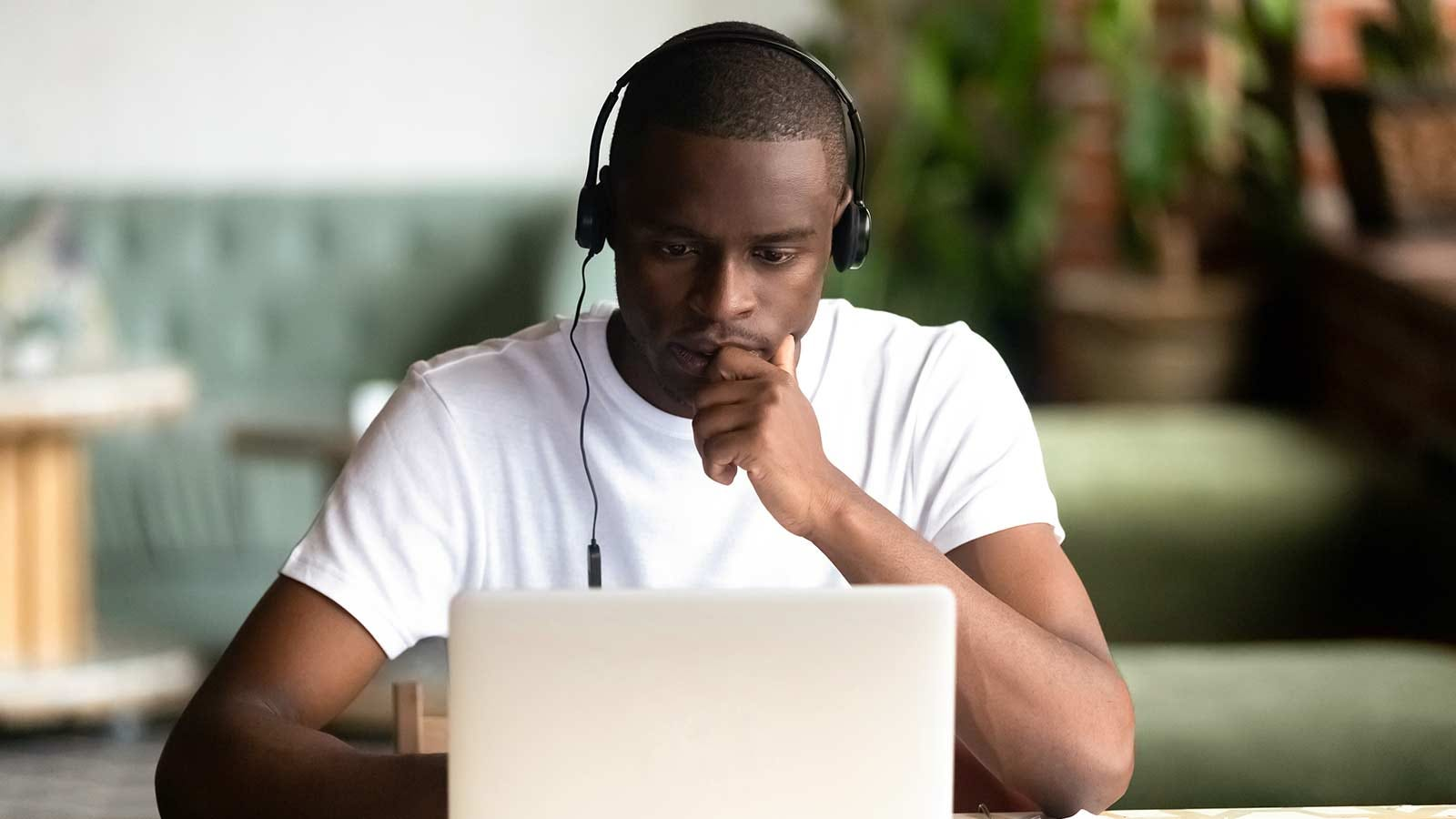 man studying intently while working on an online class