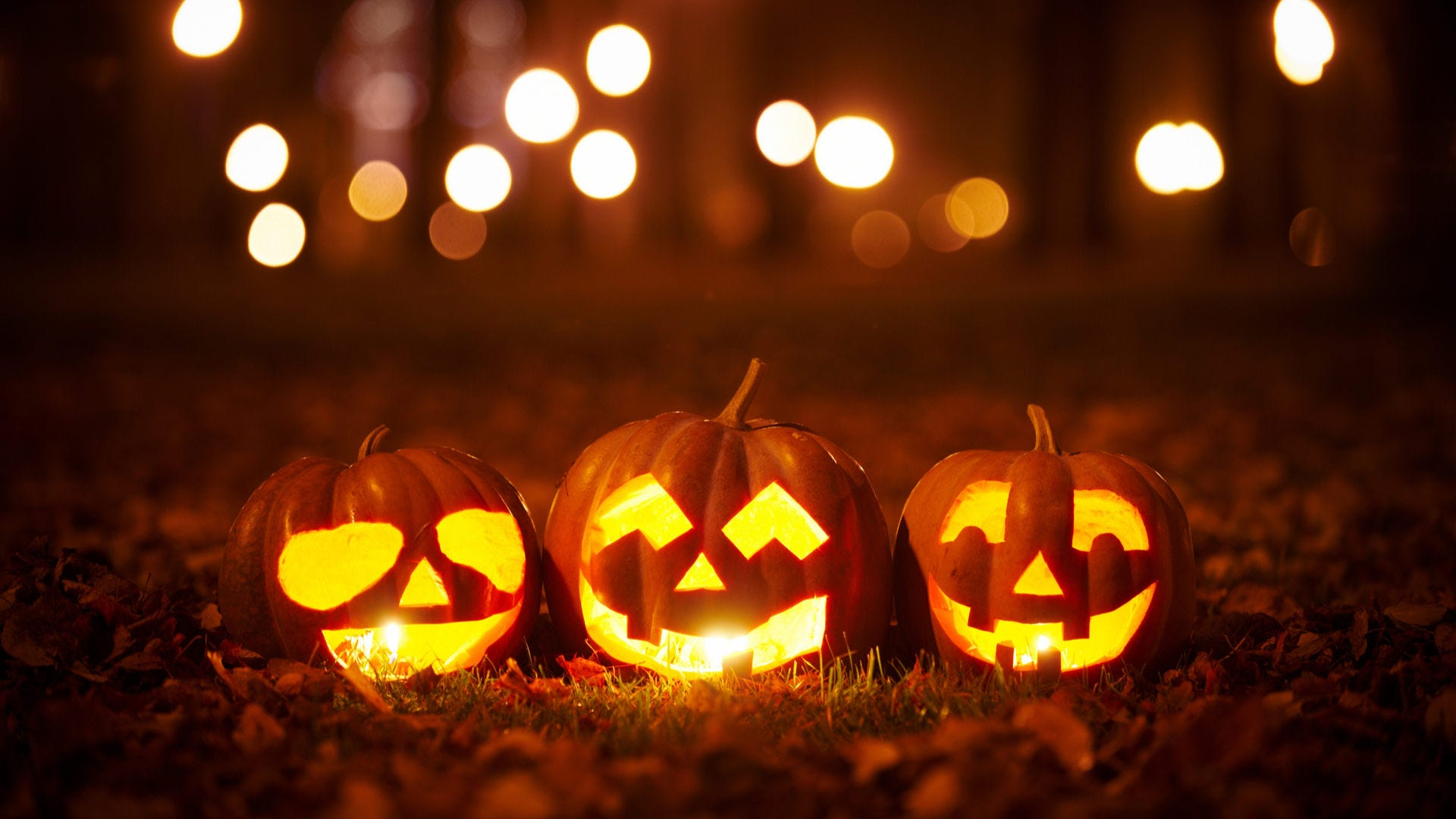 Some carved pumpkins sitting on grass at night.