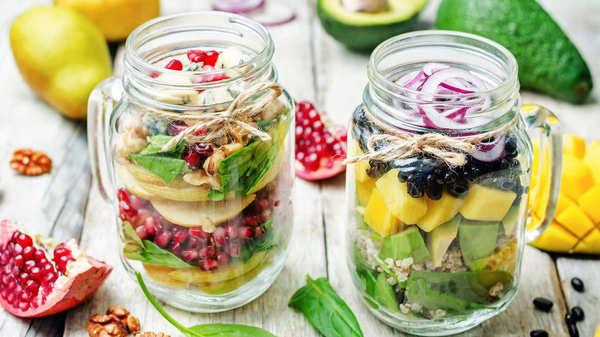 Two salads packed in mason jars.