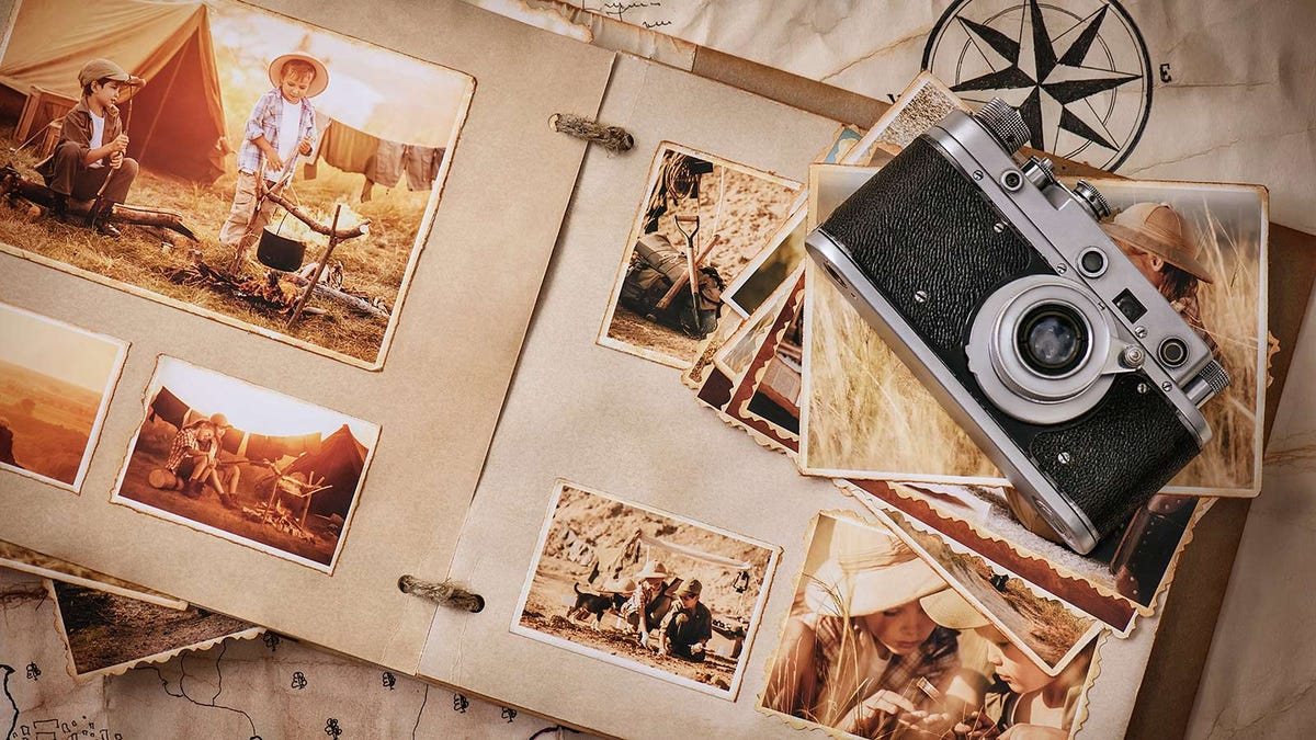 And old photo album with piles of photos and a vintage camera.