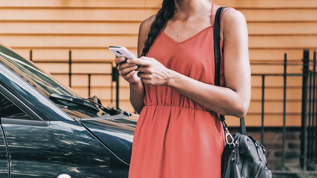 A woman standing in front of a car and holding a smartphone.