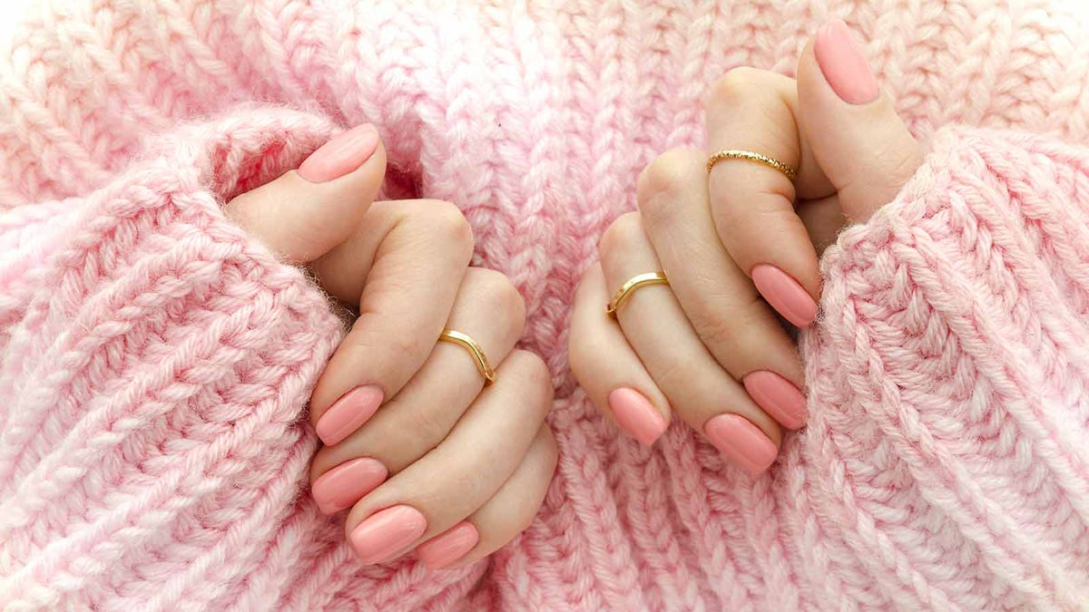 a woman's hands with pink fingernails against a pink wool sweater