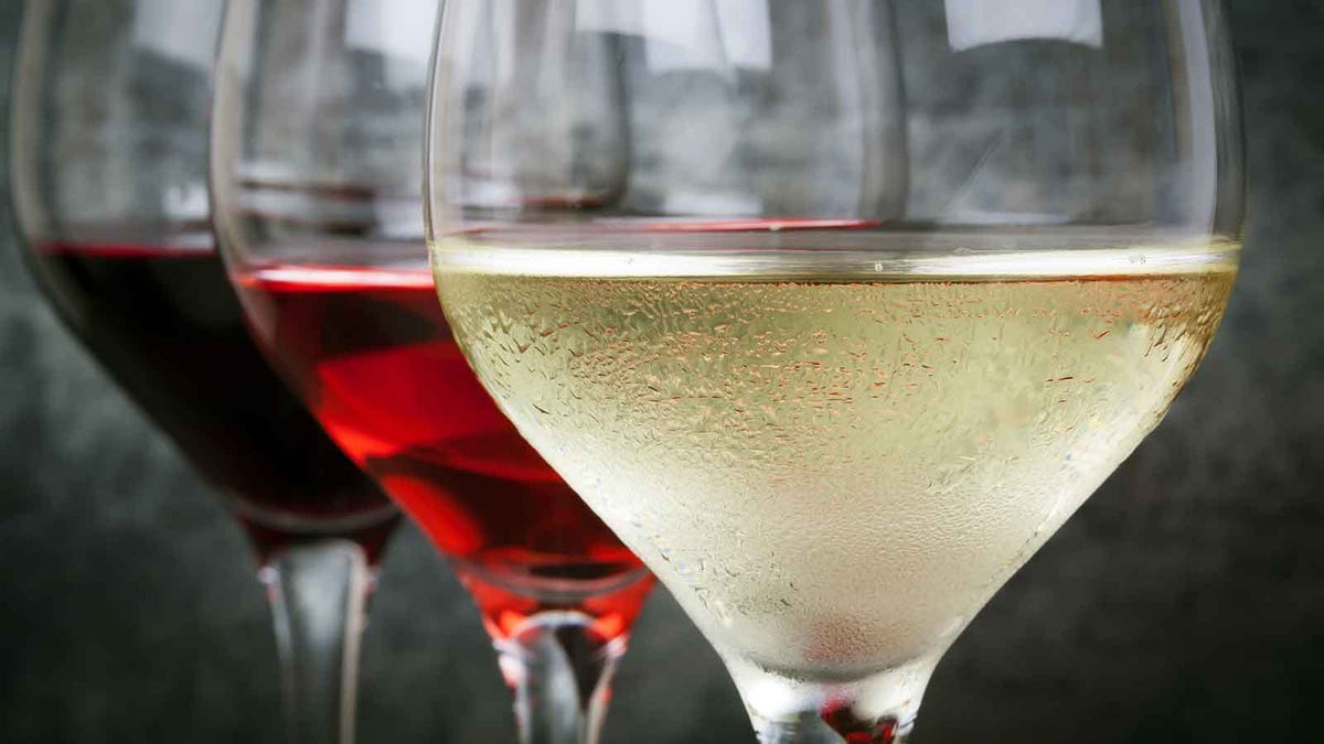 One glass of white wine next to two glasses of red.