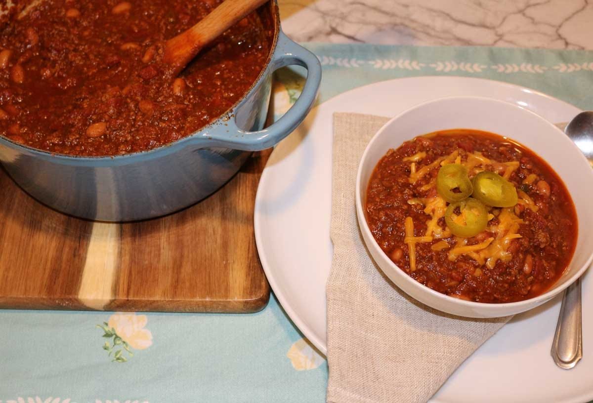 A bowl of chili with a pot of chili in the background