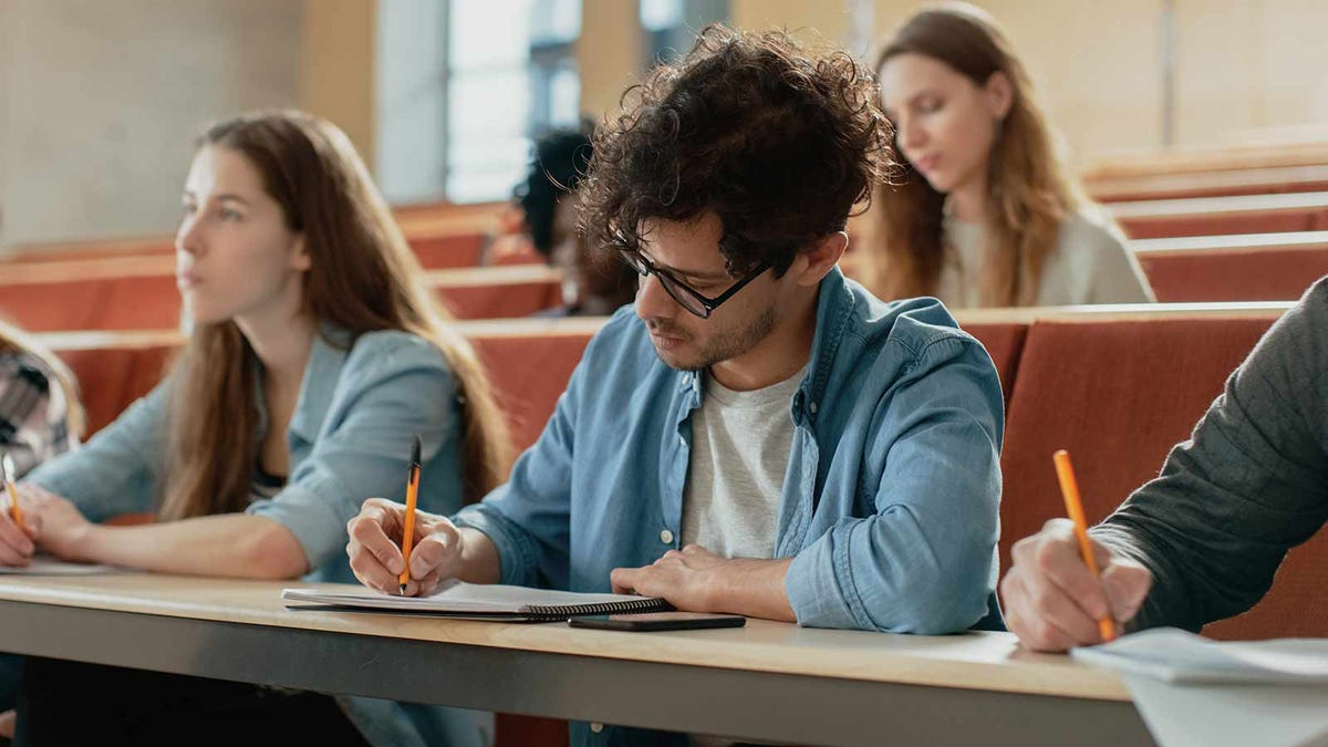 young man hand writing class notes in a lecture hall