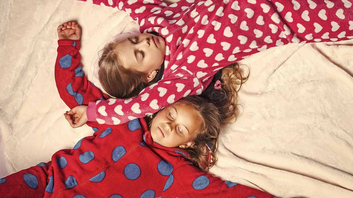 Two little girls asleep in their pajamas.