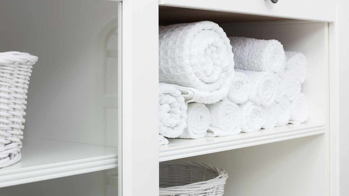 tidy linen closet with white towels