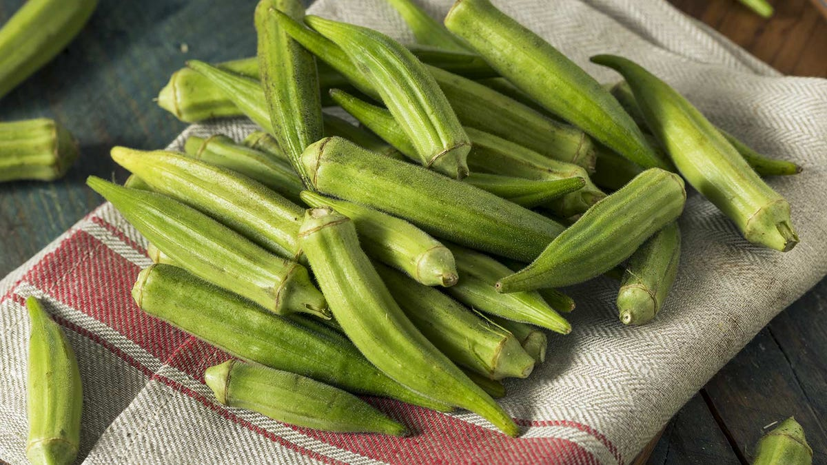 Raw green okra, piled up on a farm towel to be prepared for cooking.