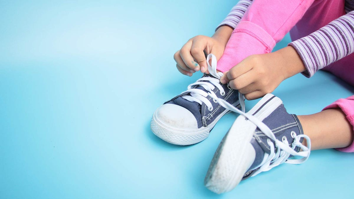 young girl learning to tie her shoes