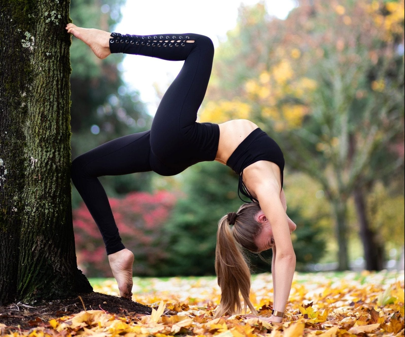 Woman doing a backbend in the park during autumn