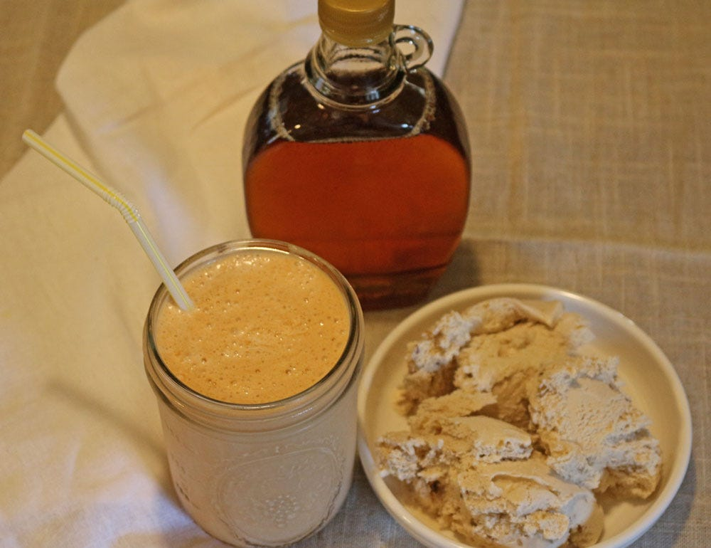 Pumpkin milkshake with a small bowl of ice cream and a bottle of maple syrup