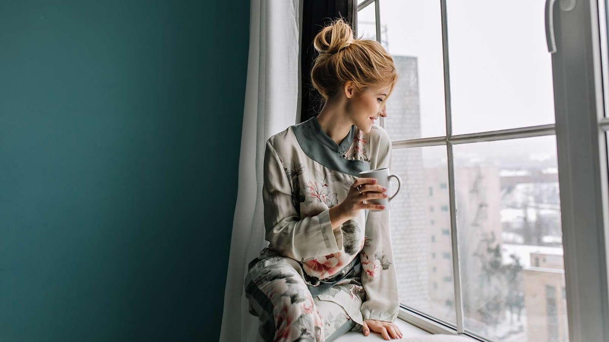 woman starting her day with a cup of tea, looking out at the snowy weather