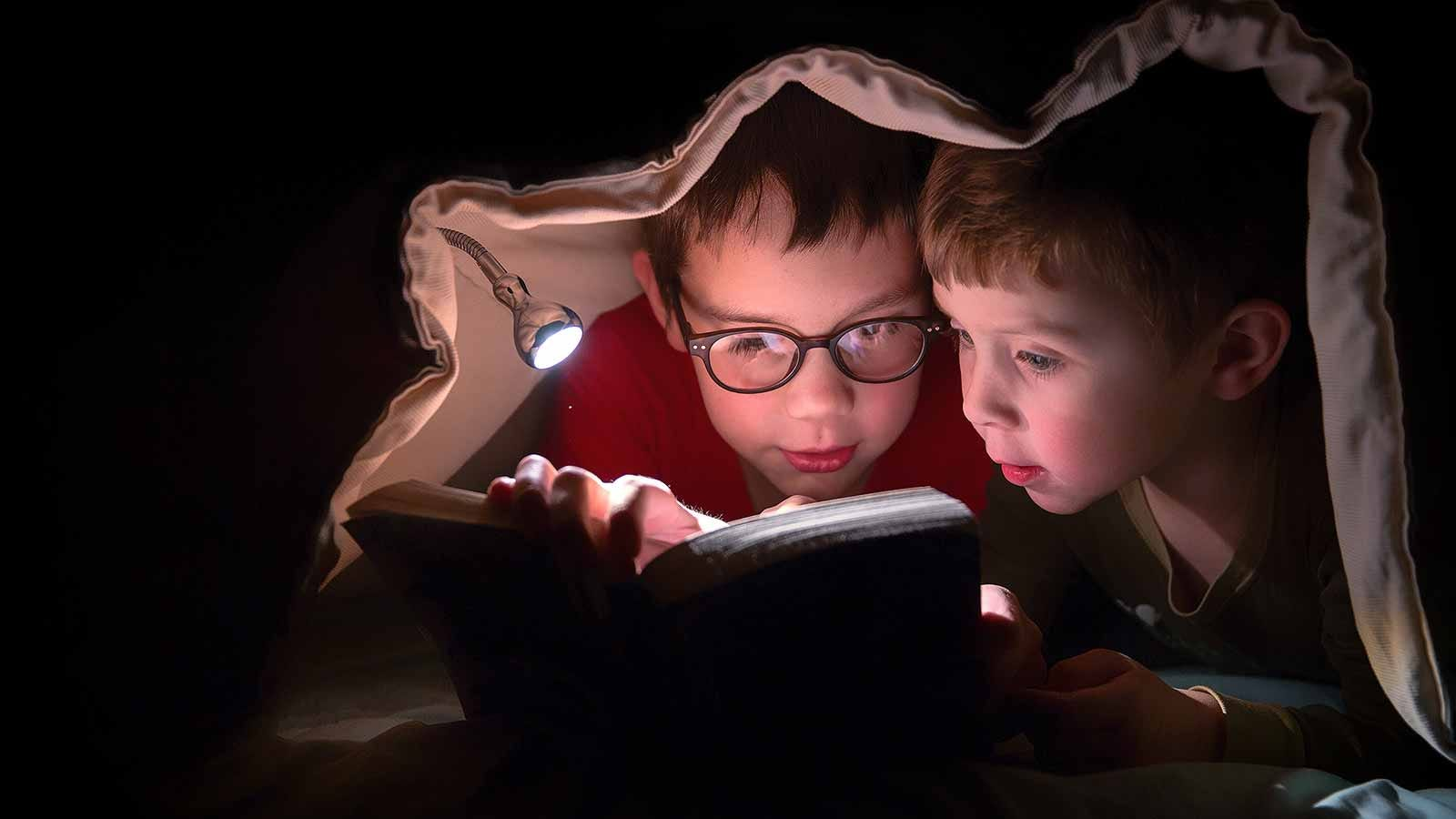 Two boys under a blanket reading a book by flashlight.