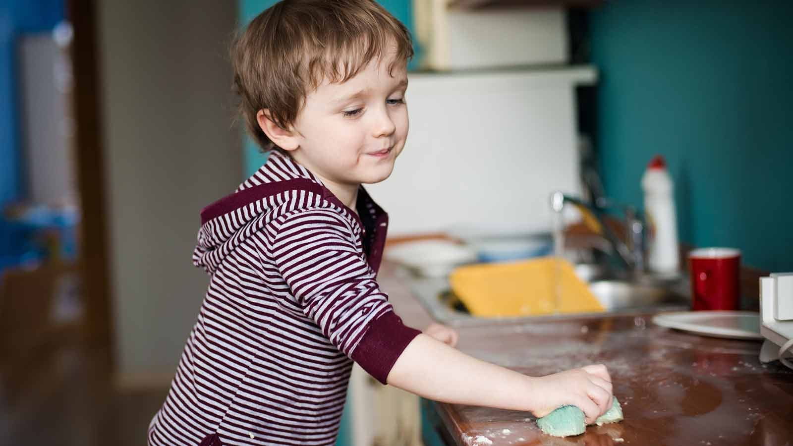 A young boy wiping down a counter in the kitchen.