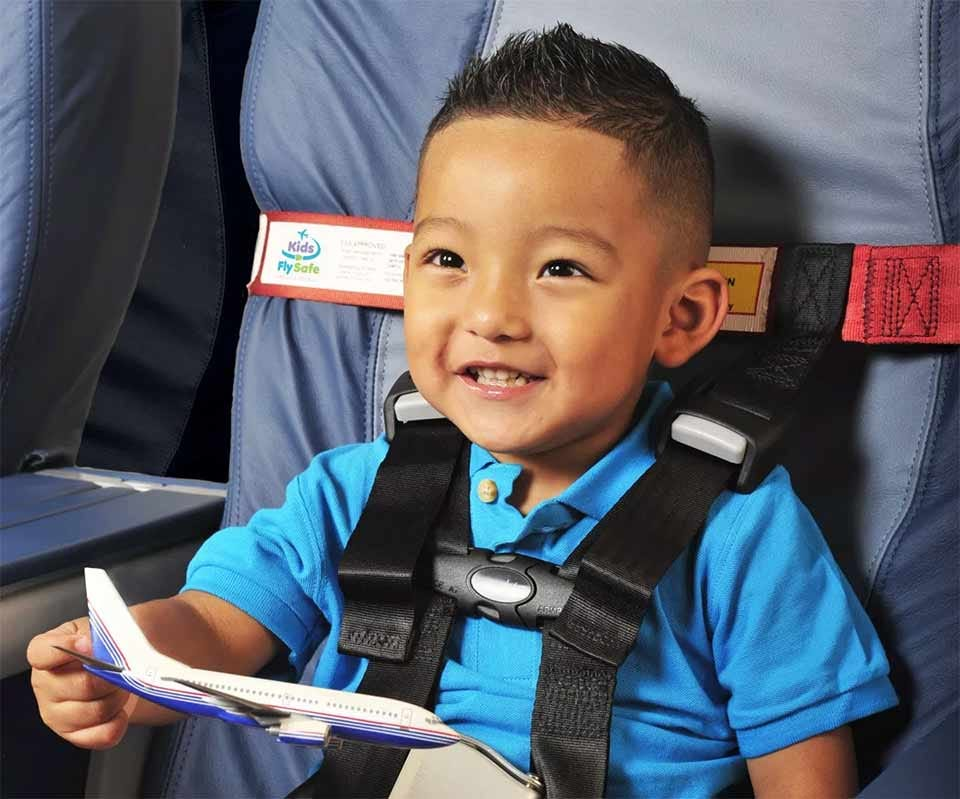 A toddler secured in a plane seat by a CARES harness.