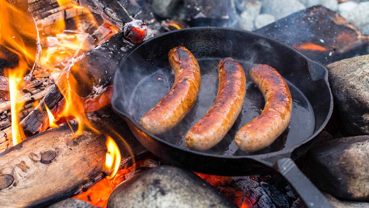 sausages cooking in a cast iron pan over a campfire